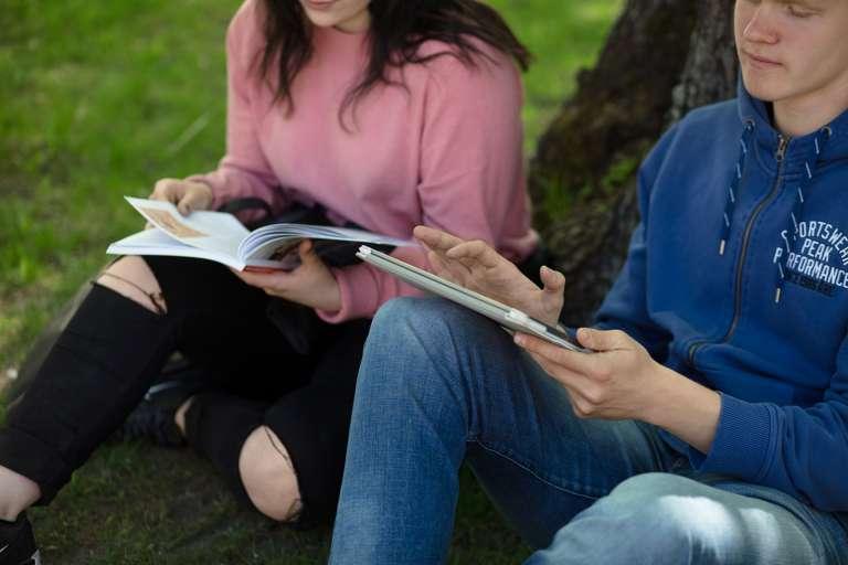 Nuoret puistossa kirjojen kanssa