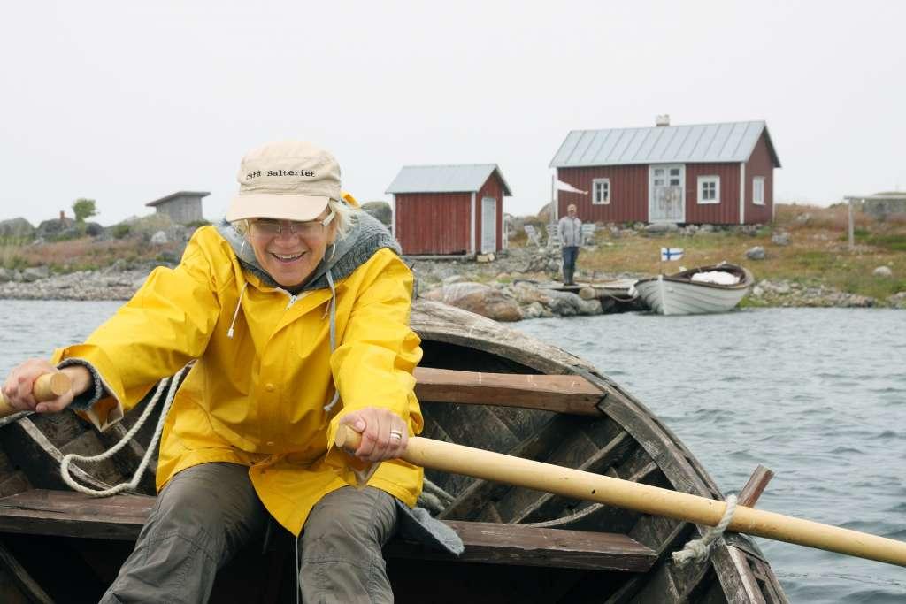 Nainen keltaisessa sadetakissa soutaa venettä Valassaarilla.