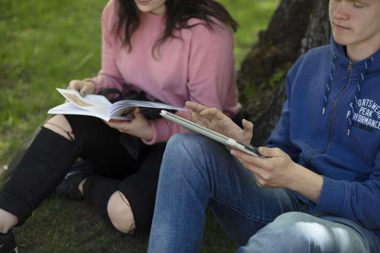 Opiskelijat nurmikolla