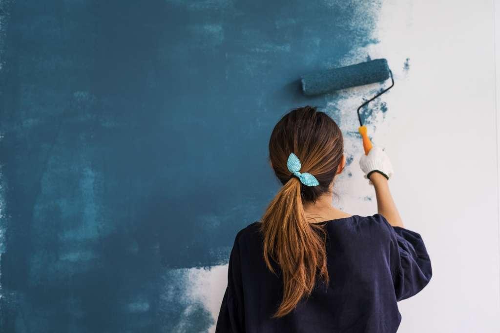 Nainen maalaa seinää
