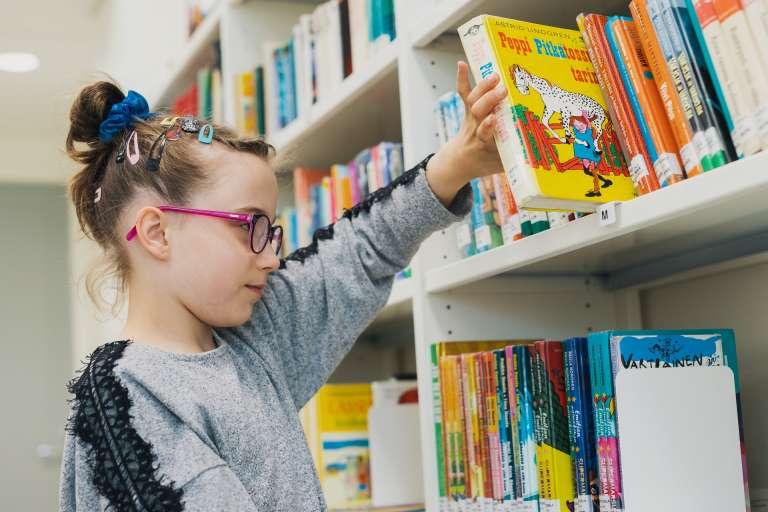 Lapsi ottaa kirjaa hyllystä