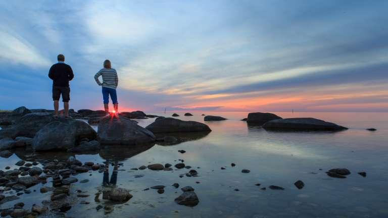Nainen ja mies seisovat merenrannalla