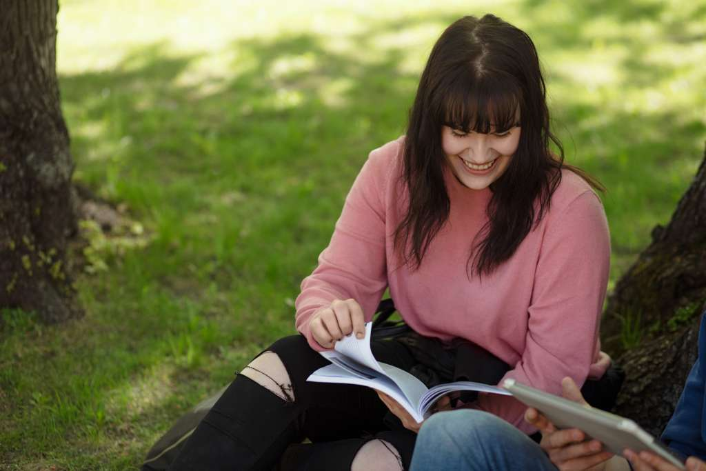 Nuoret istuvat nurmikolla kirjojen kanssa