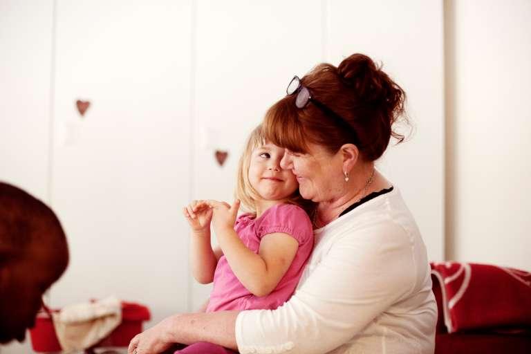 Lapsi istuu lastentarhanopettajan sylissä