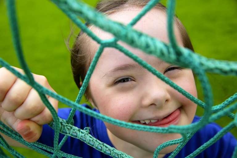 Tyttö leikkii urhielukentällä