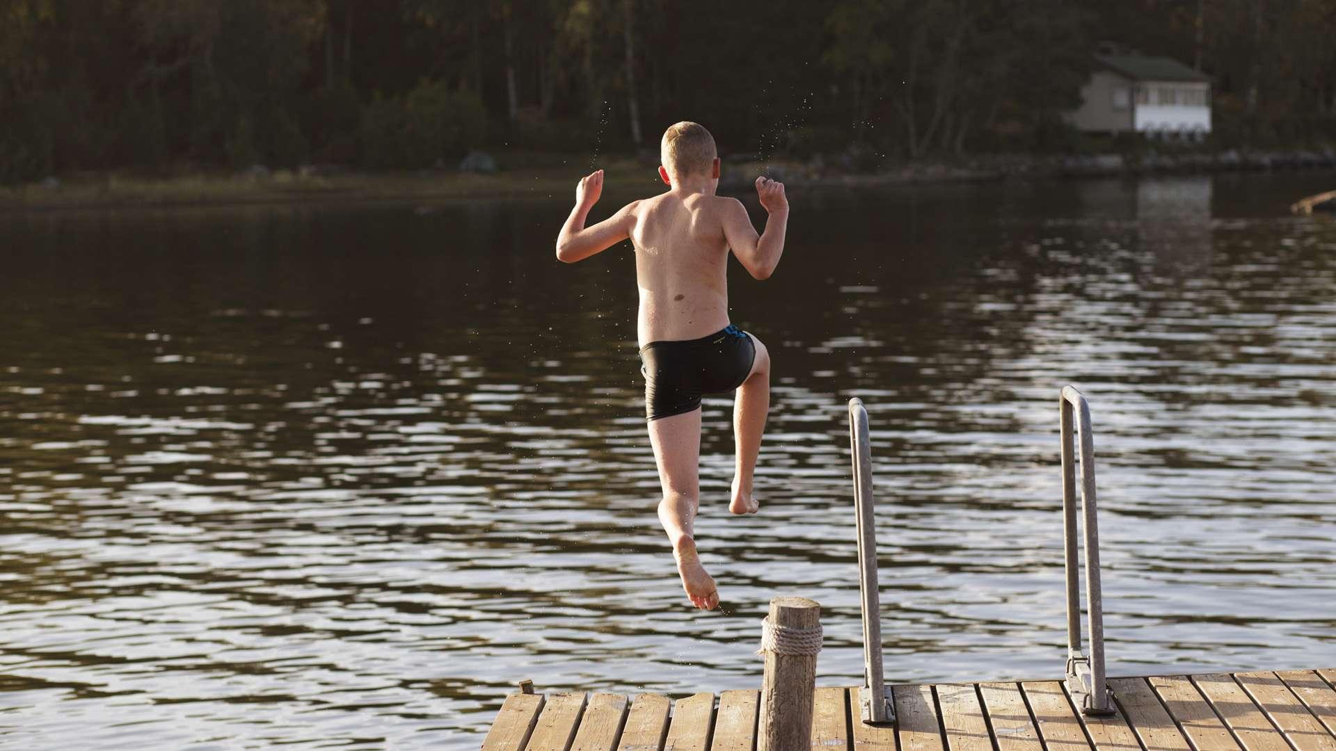 Pojken hoppar i vattnet