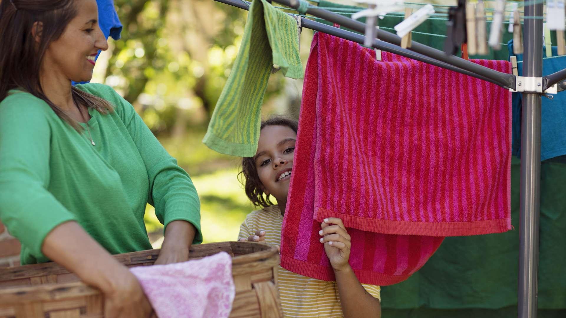 Flicka sätter tvätten ut med mamma