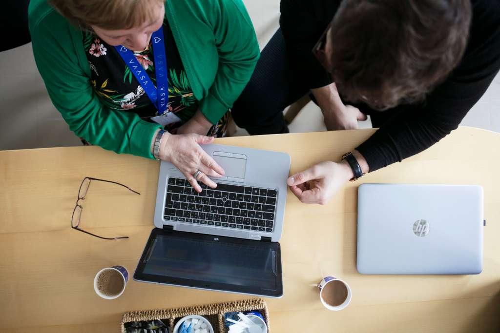 Kaksi ihmistä työskentelee tietokoneella