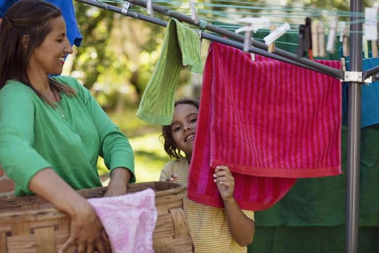 äiti ja lapsi ripustaa pyykkiä