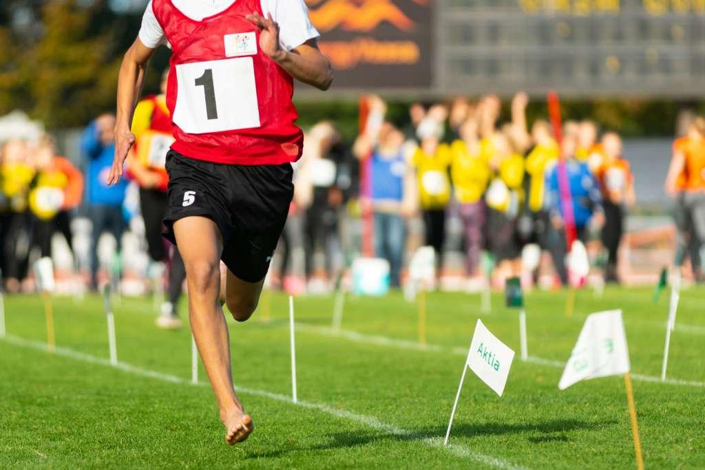 Lapsi juoksee urheilukentällä