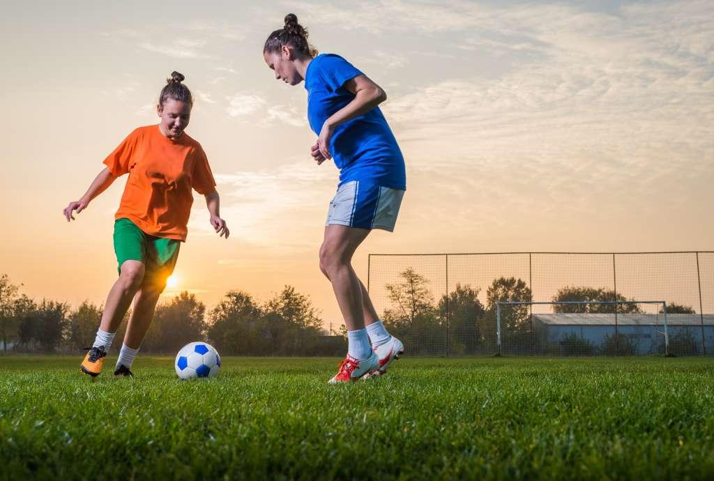 Kaksi tyttöä pelaa jalkapalloa