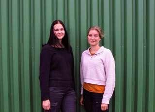 Kaksi nuorta naista seisoo ulkona vihreän seinän edessä.