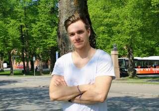 Mies seisoo puistikolla.