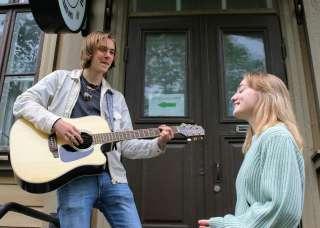 Mies soittaa kitaraa ja nainen laulaa kadulla.