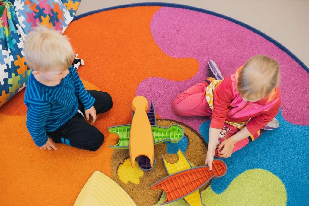 lapset leikkivät matolla