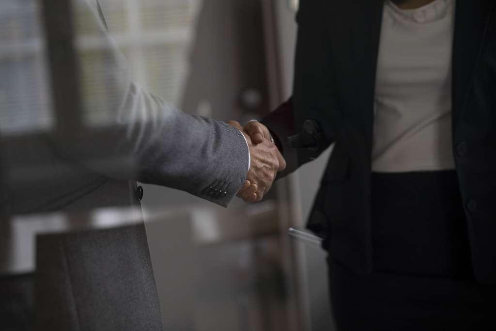 Två människor skakar hand