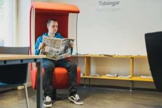 Mies lukee lehteä kirjastolla