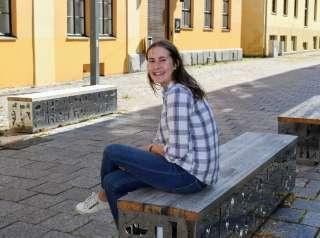 Nainen istuu hymyillen penkillä kadulla