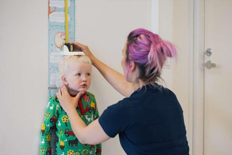Hoitaja mittaa lapsen pituutta