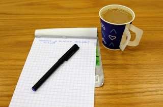Kahvikuppi ja muistilehtiö pöydällä