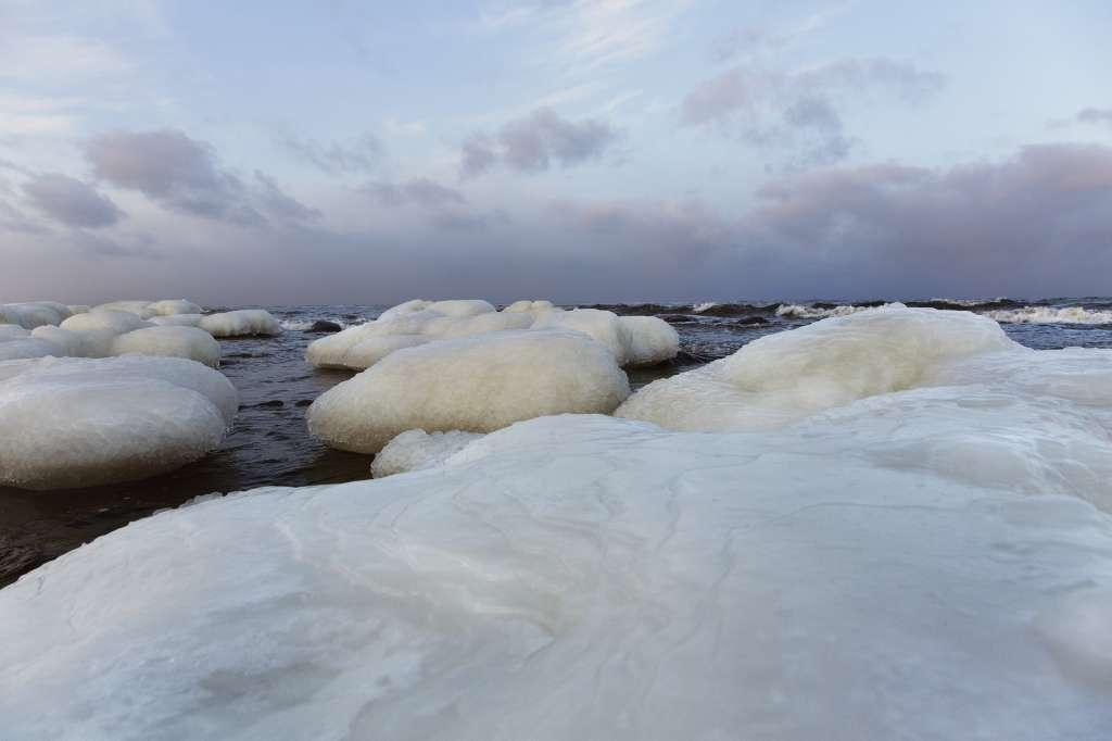 Stenar i havet täcks av ett islager i Kvarkens skärgård.