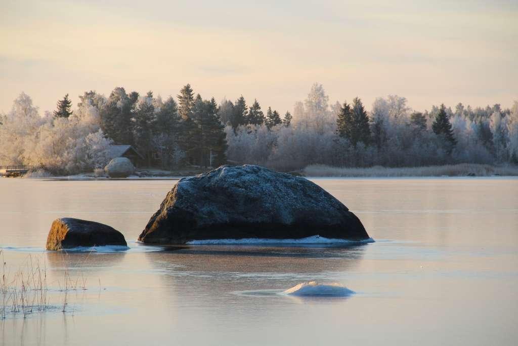 Suuri kivi jäätyneessä meressä, ja taustalla kuurainen metsä.