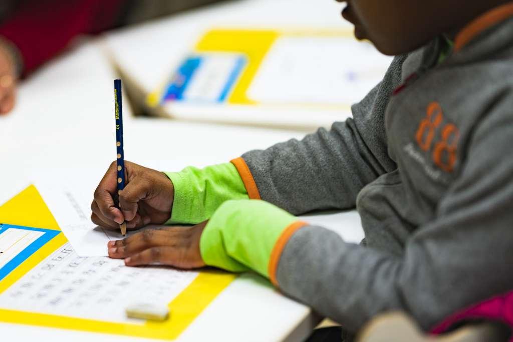 Lapsi kirjoittaa koulussa
