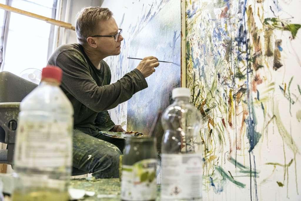 Taiteilija maalaa teosta