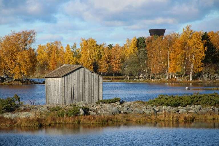 Saltkaretin näkötorni ja harmaa venevaja Bodbackin vanhasta satamasta katsottuna ruskan aikaan.