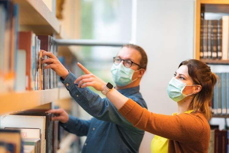 Mies ja nainen kirjastossa maskit päällä.