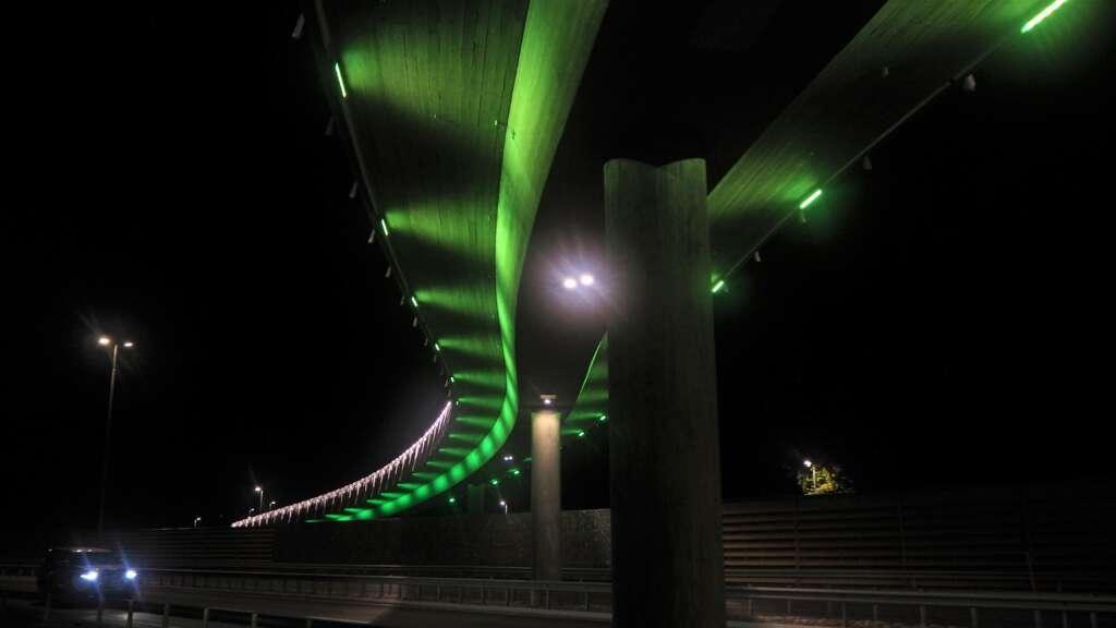 Alskatientien kävelysilta vihreäksi valaistuna.