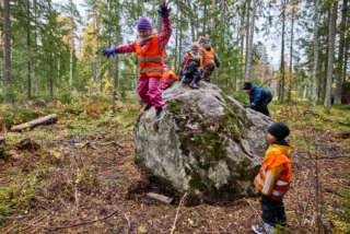 Lapset hyppivät ja kiipeilevät isolla kivellä metsässä.